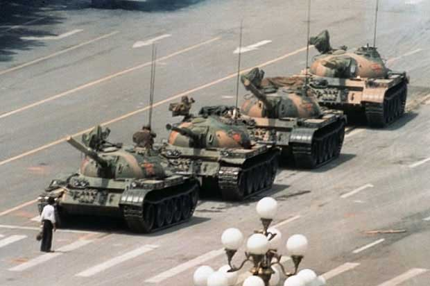 Man confronting parade of army tanks